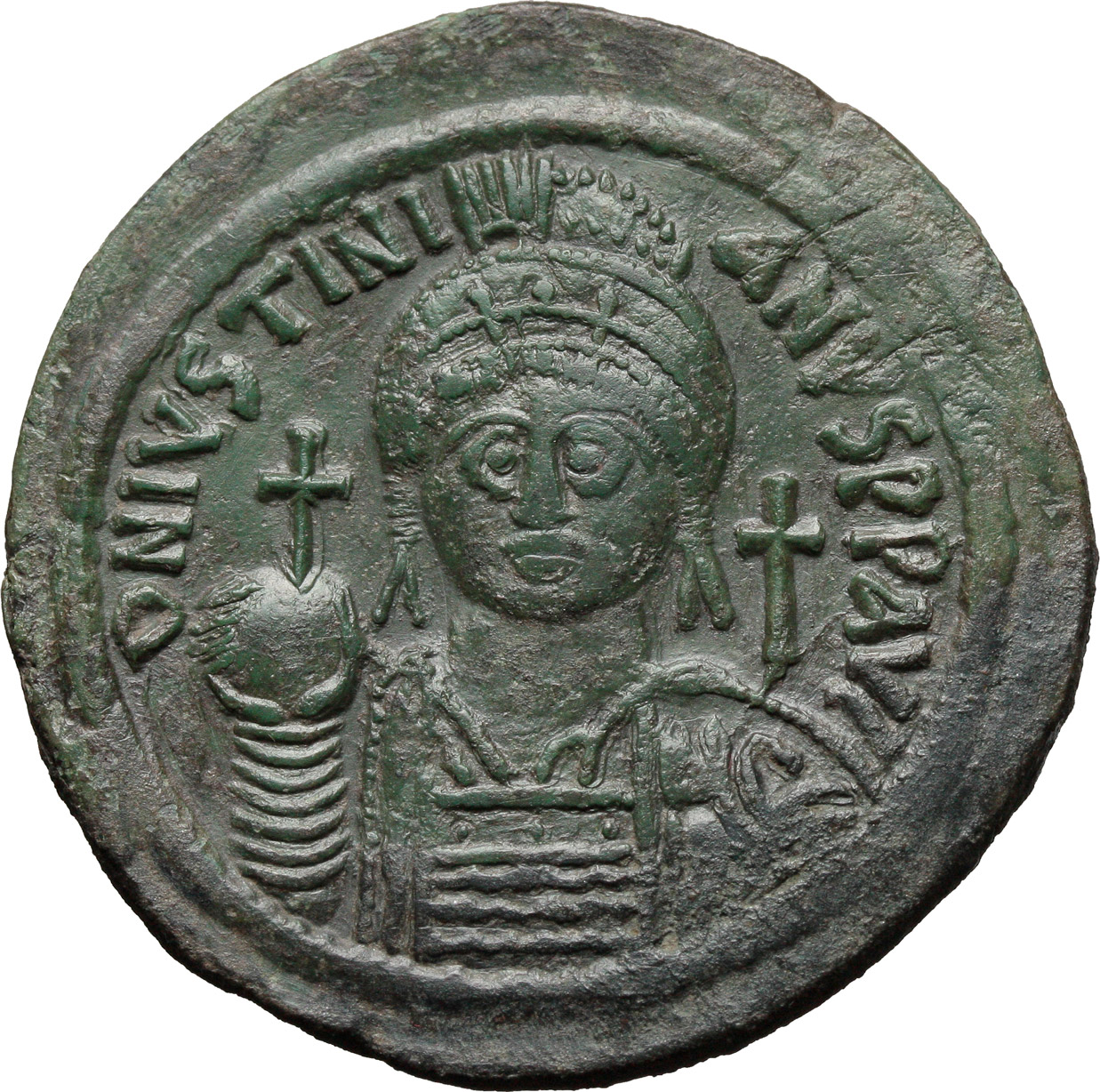D/ Justinian I (527-565).  AE Follis, Cyzicus mint. Obv. DN IVSTINIANVS PP AVG. Helmeted and cuirassed bust facing, holding globus cruciger and shield; to right, cross. Rev. Large M between A/N/N/O e X/II/I; above, cross; below, A; in exergue, KYZ. DOC 164-81. Sear 207. AE. g. 22.04  mm. 42.00   Rare in this condition, green patina. About EF.