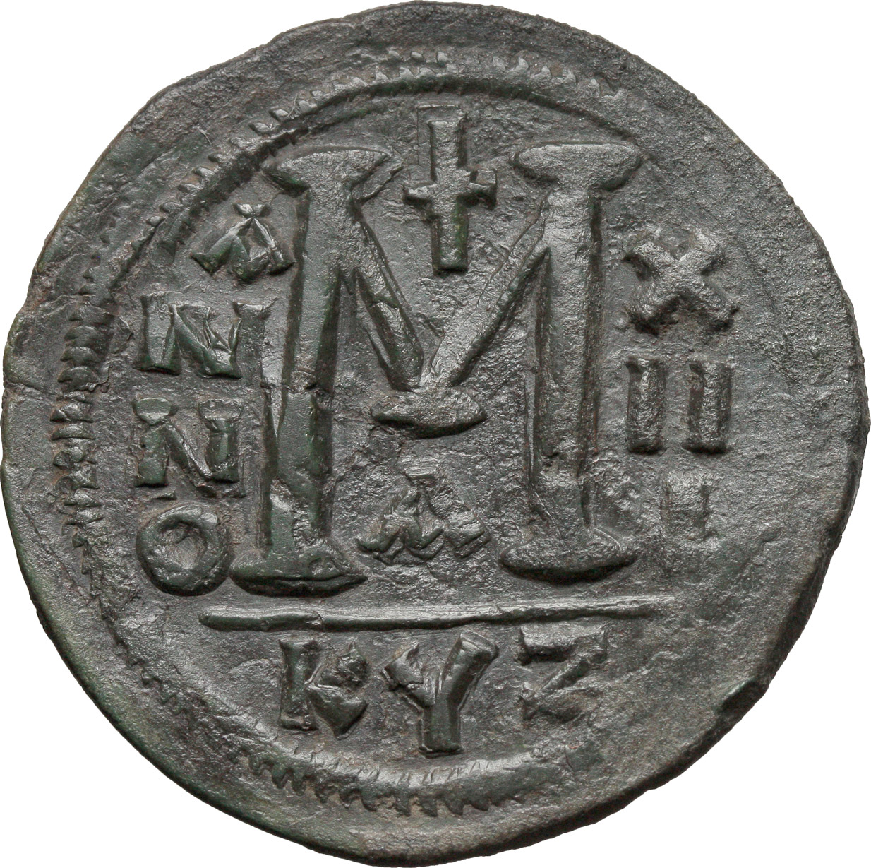 R/ Justinian I (527-565).  AE Follis, Cyzicus mint. Obv. DN IVSTINIANVS PP AVG. Helmeted and cuirassed bust facing, holding globus cruciger and shield; to right, cross. Rev. Large M between A/N/N/O e X/II/I; above, cross; below, A; in exergue, KYZ. DOC 164-81. Sear 207. AE. g. 22.04  mm. 42.00   Rare in this condition, green patina. About EF.