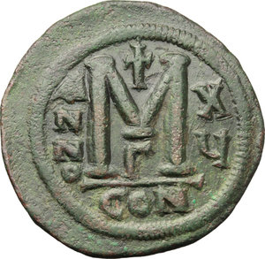R/ Justinian I. (527-565).  AE Follis, Constantinople mint. Obv. DN IVSTINIANVS PP AVI. Helmeted and cuirassed bust facing, holding globus cruciger and shield; to right, cross. Rev. Large M between A/N/N/O and X/Y; above, cross; beneath, Γ; in exergue, CON. D.O. 37-61. Sear 163. AE. g. 23.00  mm. 38.00   A superbe example. Dark green patina. Light traces of smoothing, otherwise about EF/EF.