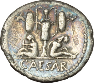 Julius Caesar.  AR Denarius, 46-45 BC. Obv. Diademed head of Venus right, Cupid on shoulder. Rev. Two captives seated at sides of trophy with oval shield and carnyx in each hand; in exergue, CAESAR. Cr. 468/1. AR. g. 3.59  mm. 19.50  Scarce. Banker s mark on obverse. Perfectly centred on a broad flan. Iridescent tone. VF.