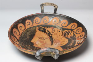 R/  Large Apulian kylix. Decorated with female head left, hair in sphendone, wave running around. 3rd century BC. H 8,2 cm (with handles), Ø 27 cm (with handles).