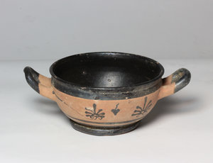 R/  Apulian black-glazed figure kylix. Decorated with two palmettes and ivy tendril. 3rd century BC. Intact. H 6,8 cm, Ø 18,5 (with handles).