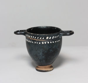 R/  Gnathia-Ware Skyphos. The body decorated with vine and ivy tendrils. Apulia, 4th century BC. H. 9 cm. Intact.