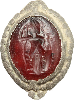 D/  Red carnelian intaglio depicting Athena standing left, in original silver ring bezel. Roman period, 1st-3rd century AD. 14 x 11 mm.
