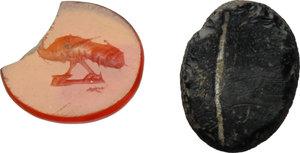 D/  Multiple lot of 2 gems: orange carnelian intaglio with figure of peacock advancing left; dark vitreous paste intaglio. Roman period, 2nd-3rd century AD. 8.5 x 7.5 mm., 9 x 7 mm.