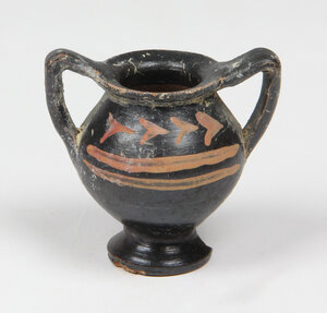 obverse: Greek miniature amphora.   A ceramic blackware miniature amphora, both faces with red painted floral motifs. 5th-3rd century BC.   55 mm height